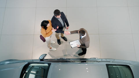 Top view of car buyers shaking hands with dealer hugging indoors in dealership Live Action