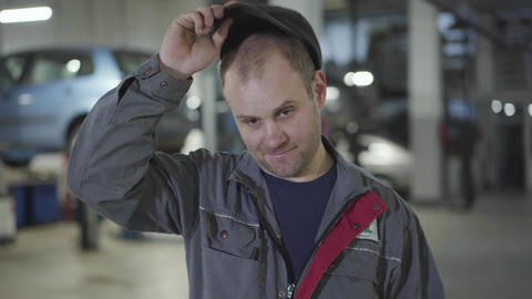 Close-up of adult Caucasian maintenance engineer taking off cap and wiping Live Action