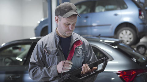 Portrait of adult Caucasian man using computer and looking around in auto repair Live Action