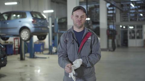 Portrait of young confident Caucasian man posing in auto repair shop Live Action