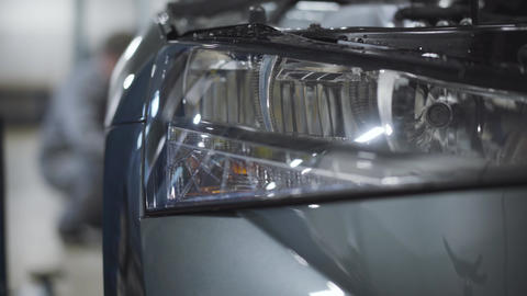 Close-up of car headlight with blurred auto mechanic tightening screws on wheel Live Action