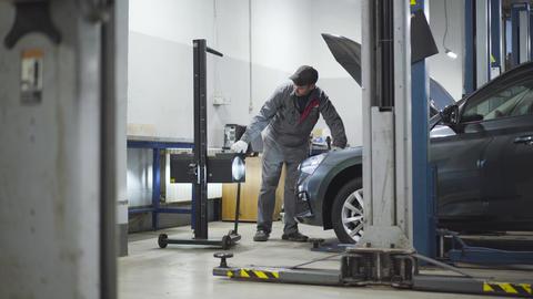 Adult professional auto mechanic adjusting lightning equipment in auto repair Live Action