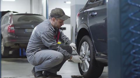 Side view of adult professional tightening screws on car wheel. Caucasian male Live Action
