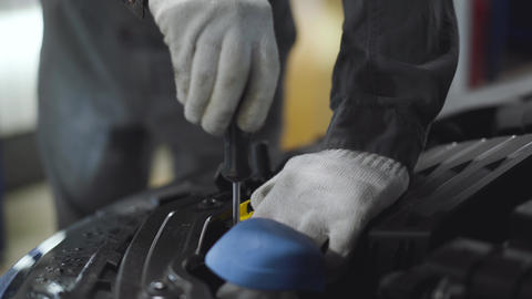 Close-up of male hands in protective gloves using screwdriver to tighten screws Live Action