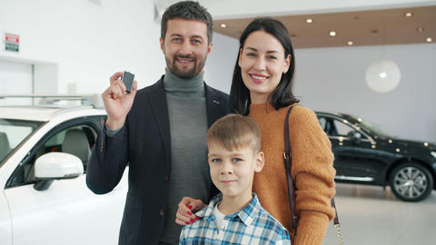 Portrait of cheerful people parents and kid standing together in automobile Live Action