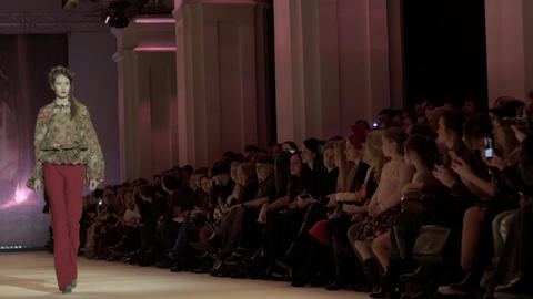Fashion show. Girl model walking on the catwalk. Slow motion Live Action