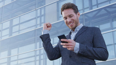 Success and achievement - happy businessman cheering looking at cell phone Live Action