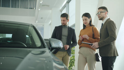 Happy man and woman talking to car dealer in dealership discussing automobiles Live Action