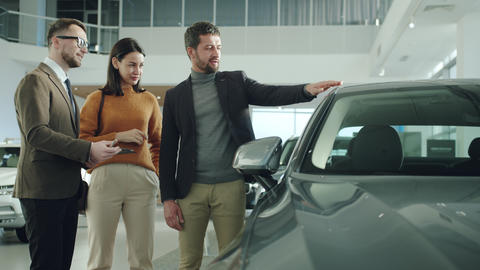 Businessman and beautiful wife choosing car in dealership talking to salesman Live Action