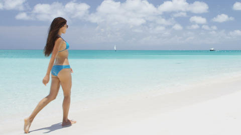 Beach life - travel vacation woman in bikini walking on perfect paradise beach Live Action