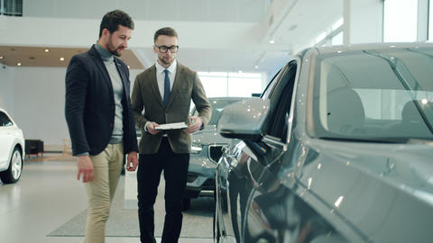 Friendly sales manager in car dealership talking to male customer showing Live Action