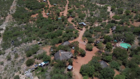 Aerial view on a small resort and a few buildings in the middle of savanna Live Action