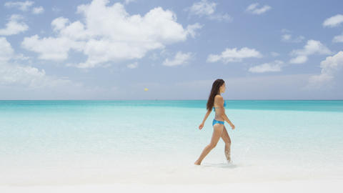 Beach travel woman relaxing in bikini walking - perfect iconic beach vacation Live Action