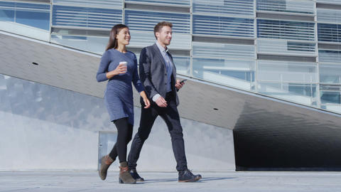 Business people walking and talking - business woman and business man outside Live Action