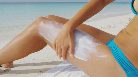 Beach woman applying sunscreen lotion on body - sun drawing protection skincare Live Action