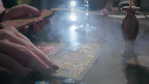The witch lays out tarot cards. Conducts a spiritualistic session, looks at the Live Action