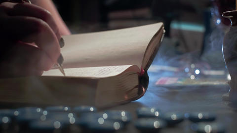 The witch is reading a magic book. Makes notes of a ritual ceremony. Conducts a Live Action