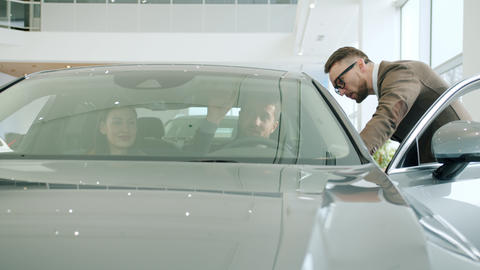 Professional car dealer talking to young couple buying automobile in dealership Live Action