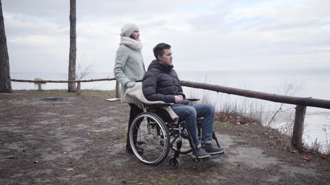 Portrait of young positive Caucasian woman touching shoulder of disabled man in Live Action