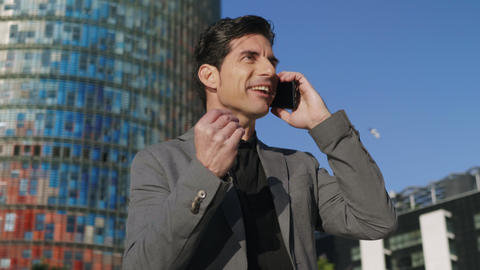 Businessman talking mobile phone at street. Executive celebrating success Live Action