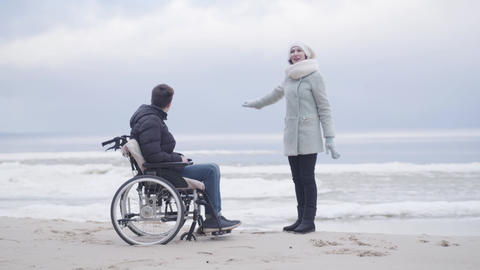 Cheerful Caucasian woman talking with boy in wheelchair and pointing away. Adult Live Action