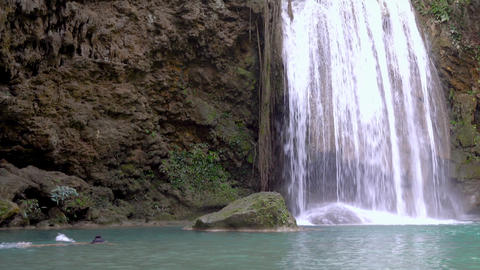 pan and zoom video of A woman swimming in Erawan waterfall. She relaxes in the beautiful nature Live Action