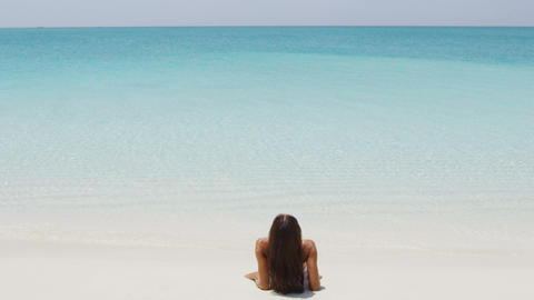 Travel beach woman sunbathing relaxing at perfect paradise beach on vacation Live Action