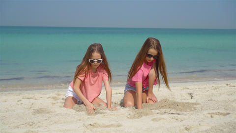 Two little happy girls have a lot of fun at tropical beach playing together Live Action
