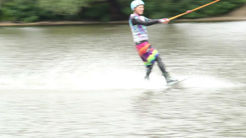 Wakeboarder riding water surface using wake board towed by cable Footage