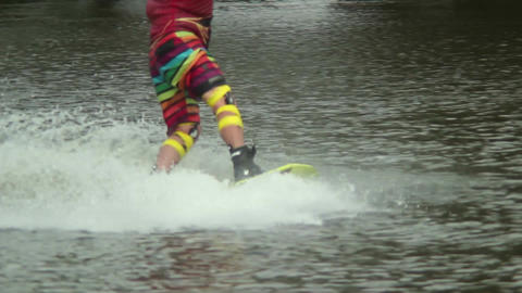 Wake-boarder in colorful sport suit rides water track splashes Footage