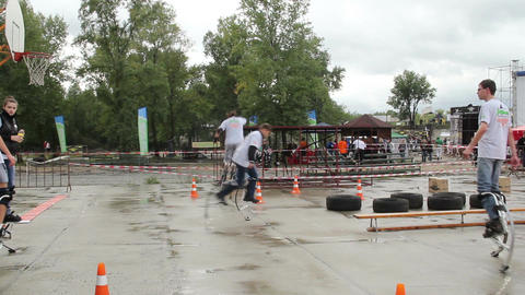 Young adult men walking on jumping stilts, jumps, running Footage