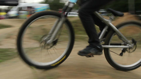 Bicycle rider BMX races difficult track, spinning wheels daytime Footage