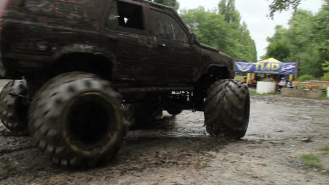 Large bigfoot driving away, wheels and glasses in dirt mud Live Action