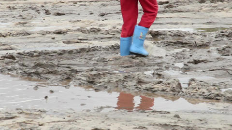 Child feet walk on puddle dirt, blue boots, children unsafety Footage