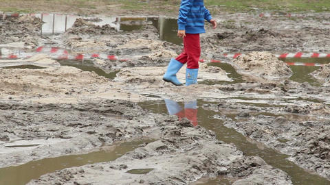 Child in boots walks on dirt puddle, children unsafety care Footage