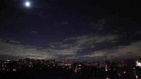 Night city timelapse, houses buildings shine lights, clouds move Footage
