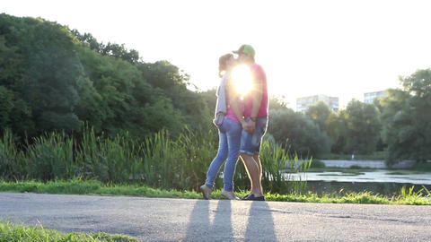 Young couple kissing at sunset, romantic love, sunshine kiss Footage