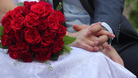 Newlyweds bride and groom on bench with bouquet of roses Footage