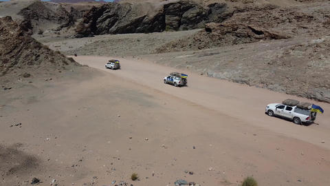 Three white SUVs are driving on a dusty road in the mountains, desert Live Action