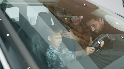 Mother, father and little boy choosing automobile in dealership touching car Live Action