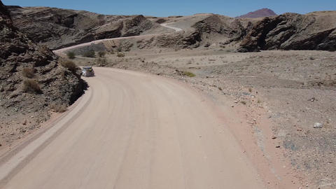 Drone footage of the rocky terrain region with dusty roads and cars driving Live Action