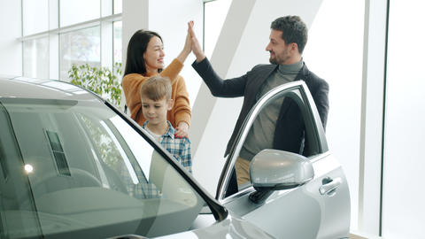 Cheerful couple and child purchasing car in showroom doing high-five opening Live Action