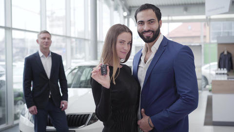 Portrait of rich multiracial family looking at camera and smiling in dealership Live Action
