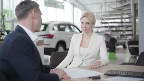 Portrait of young Caucasian blond woman in elegant suit receiving papers from Live Action