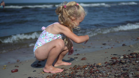 Beautiful blond girl playing with pebble stones on sea coastline. Sea waves Live Action