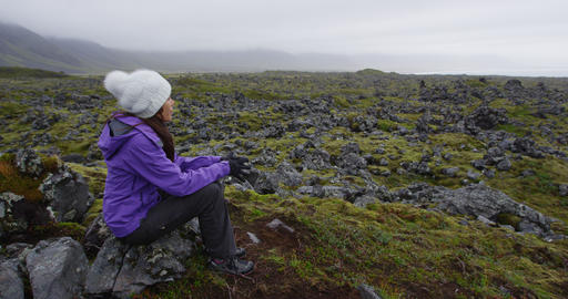Woman on hike resting on rock hiking on Iceland - Tourist hiker enjoying view Live Action
