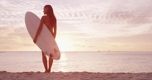 Fitness sport surfing on travel vacation - Surfer girl surfing at beach sunrise Live Action