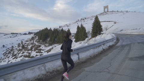 Young fitness woman jogging in the mountain with Arc of Freedom in the Live Action
