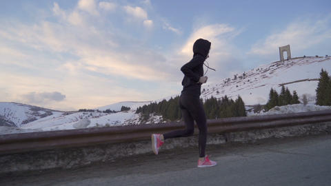Young fitness woman jogging in the snow. Arc of Freedom in the background with Live Action