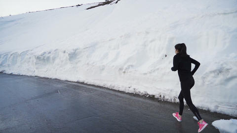 Determined energetic female jogger practicing in deep snow in the mountain Live Action